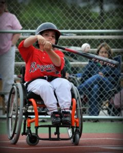 Photo of child in wheelchair hitting a baseball