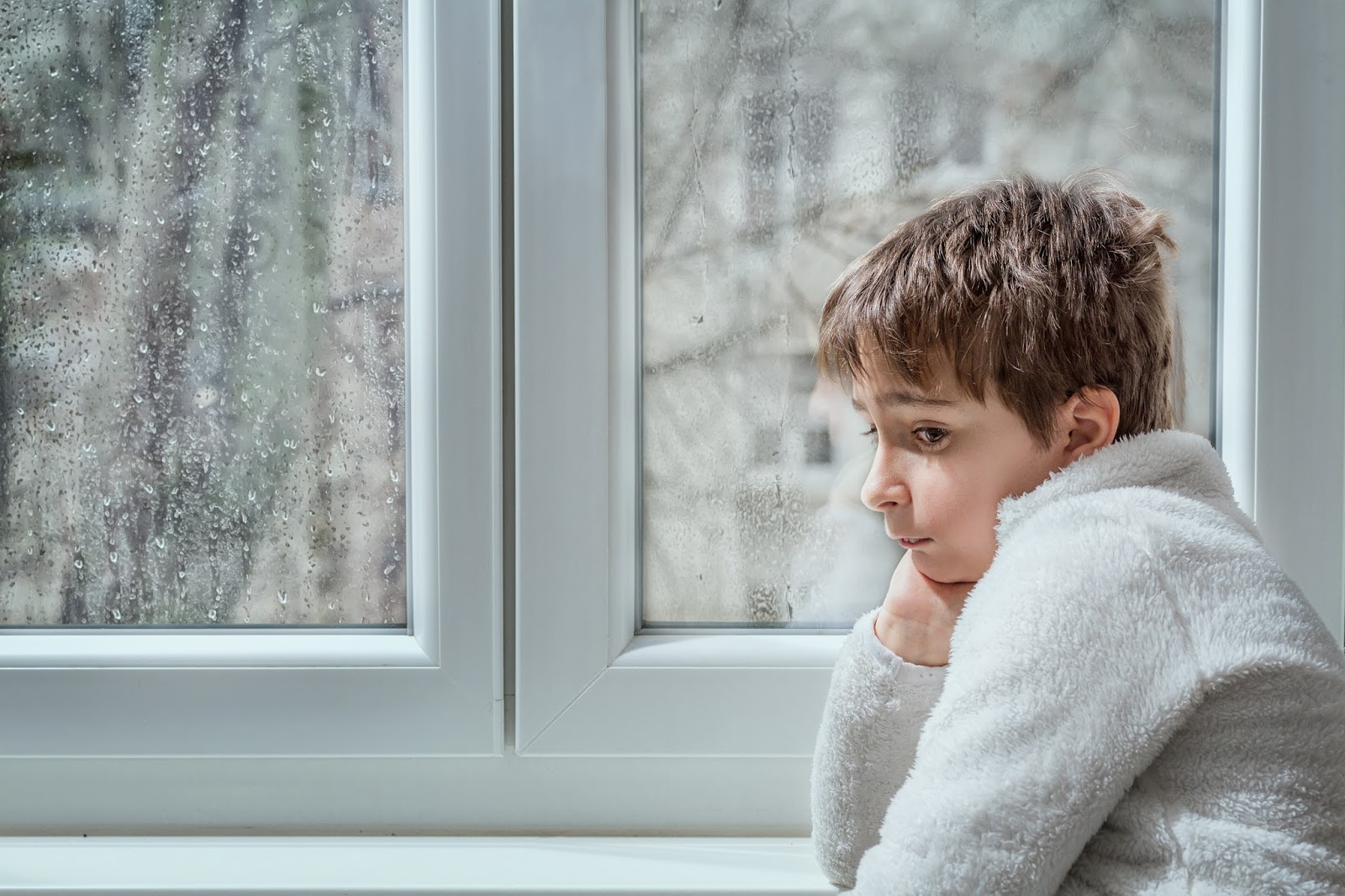 Photo of child next to a rainy window