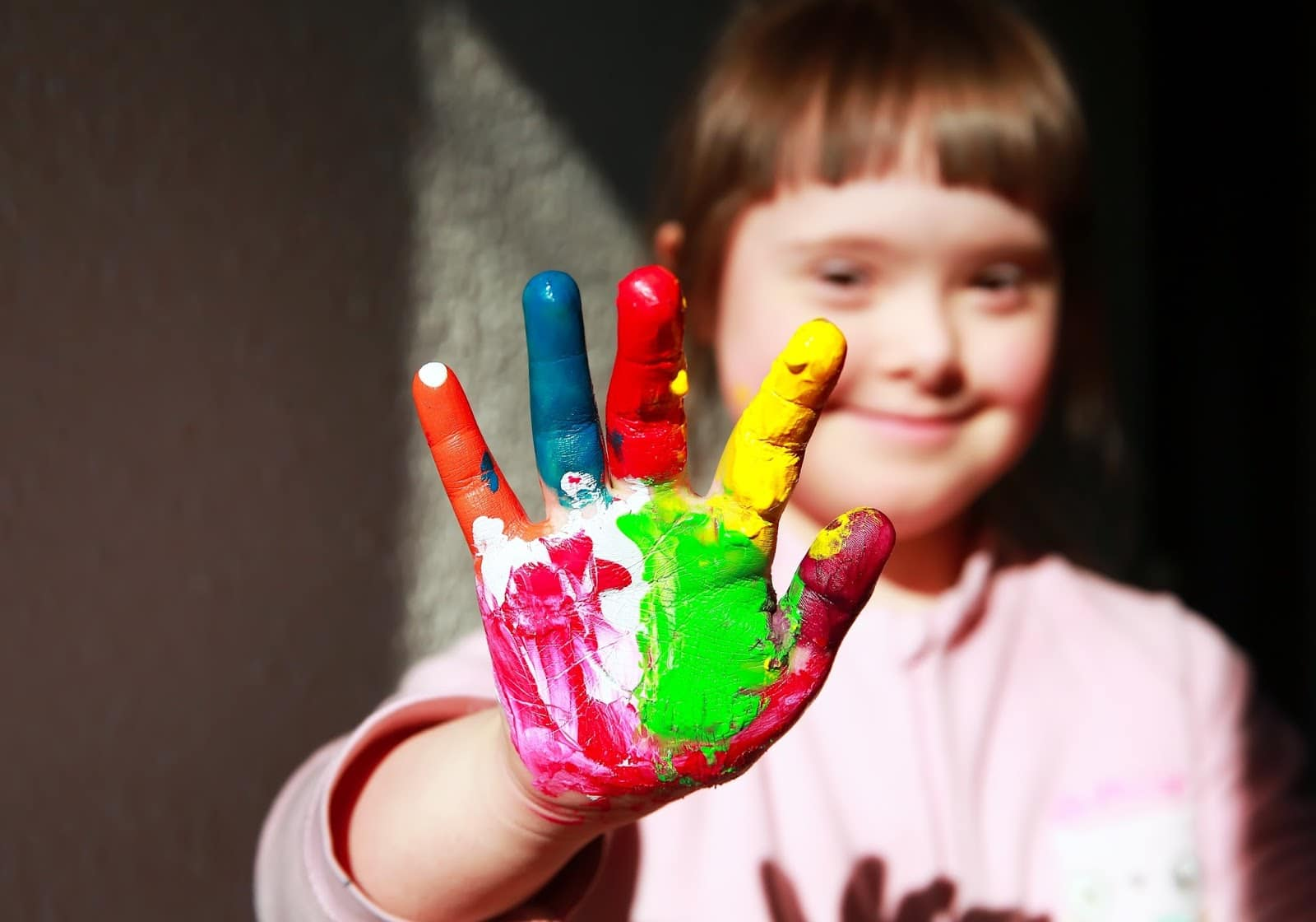 Image of girl with hand covered in fingerpaints