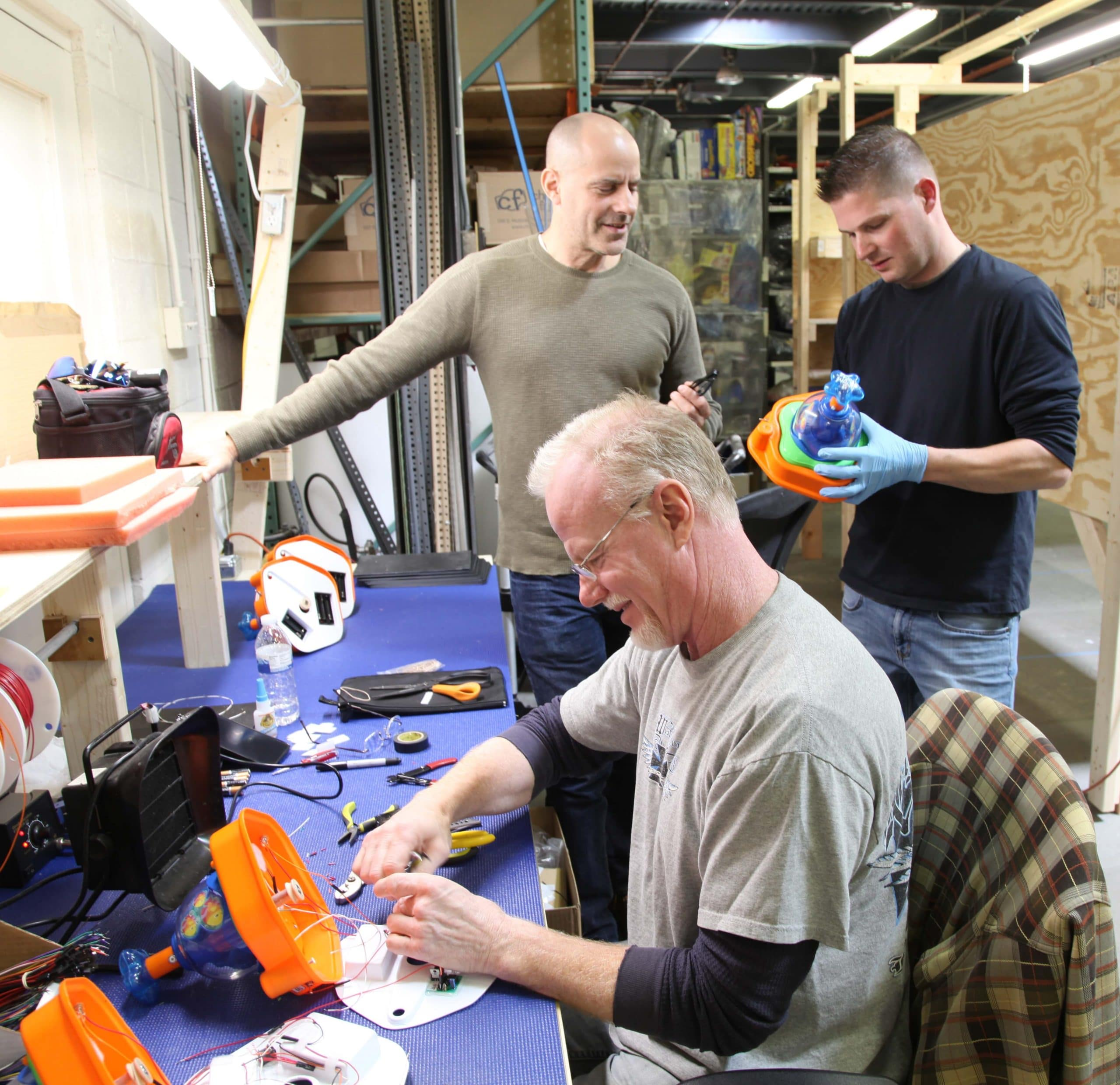 Three Enabling Devices employees building new products in our manufacturing facility