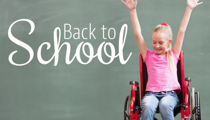 "Girl in Wheelchair in front of blackboard that says ""Back to School"""
