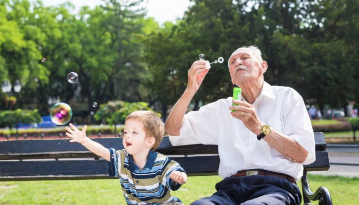 Grandfather blowing bubbles with grandson in a park