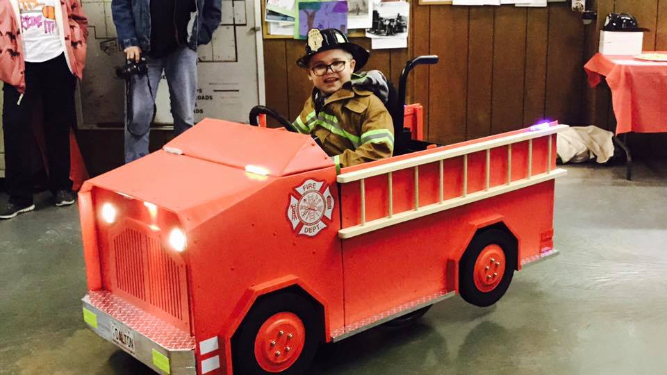 Boy in Wheelchair decorated as a Fire Truck for Halloween