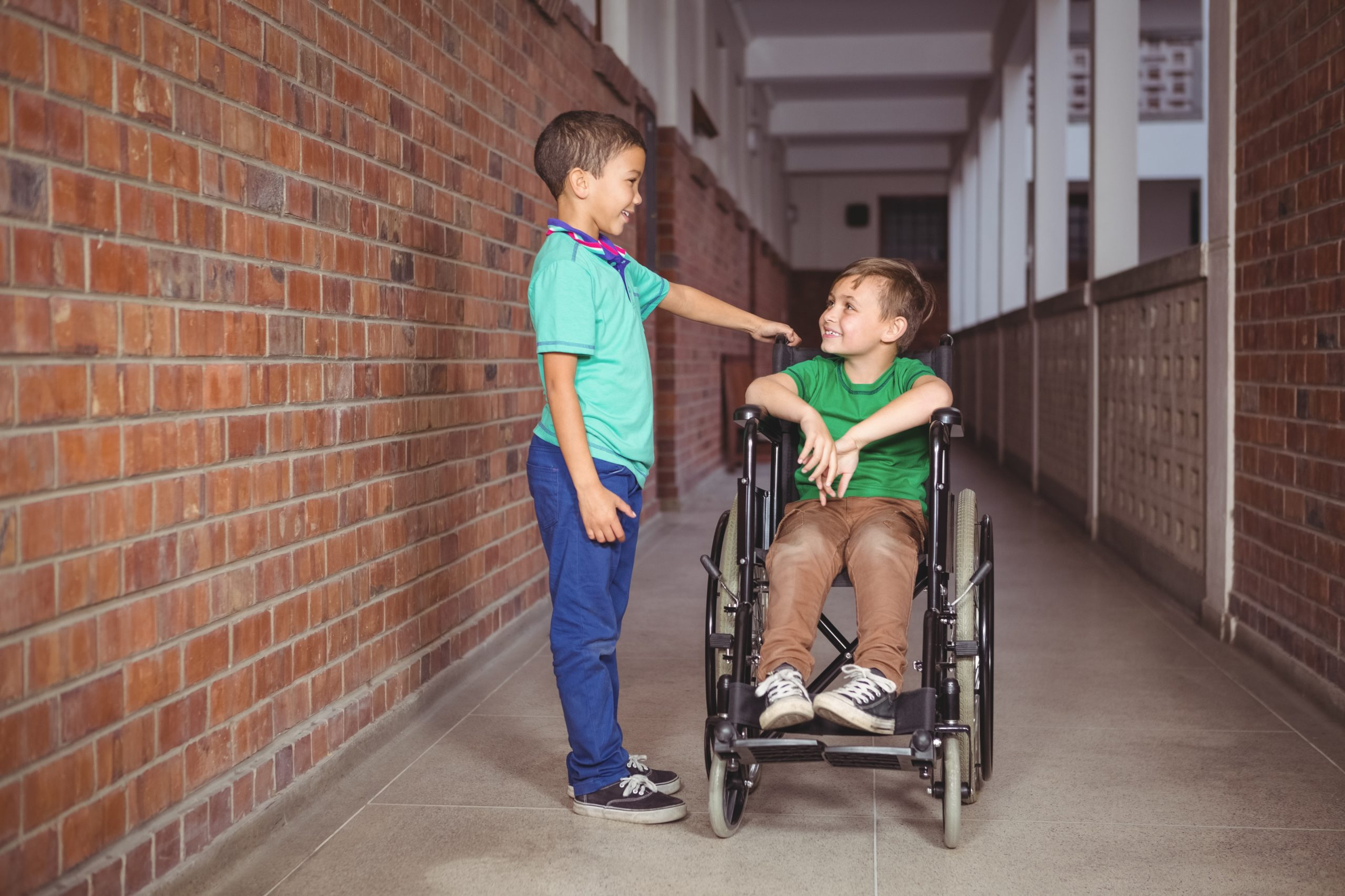 Boy in Wheelchair talks to friend in a school hallway