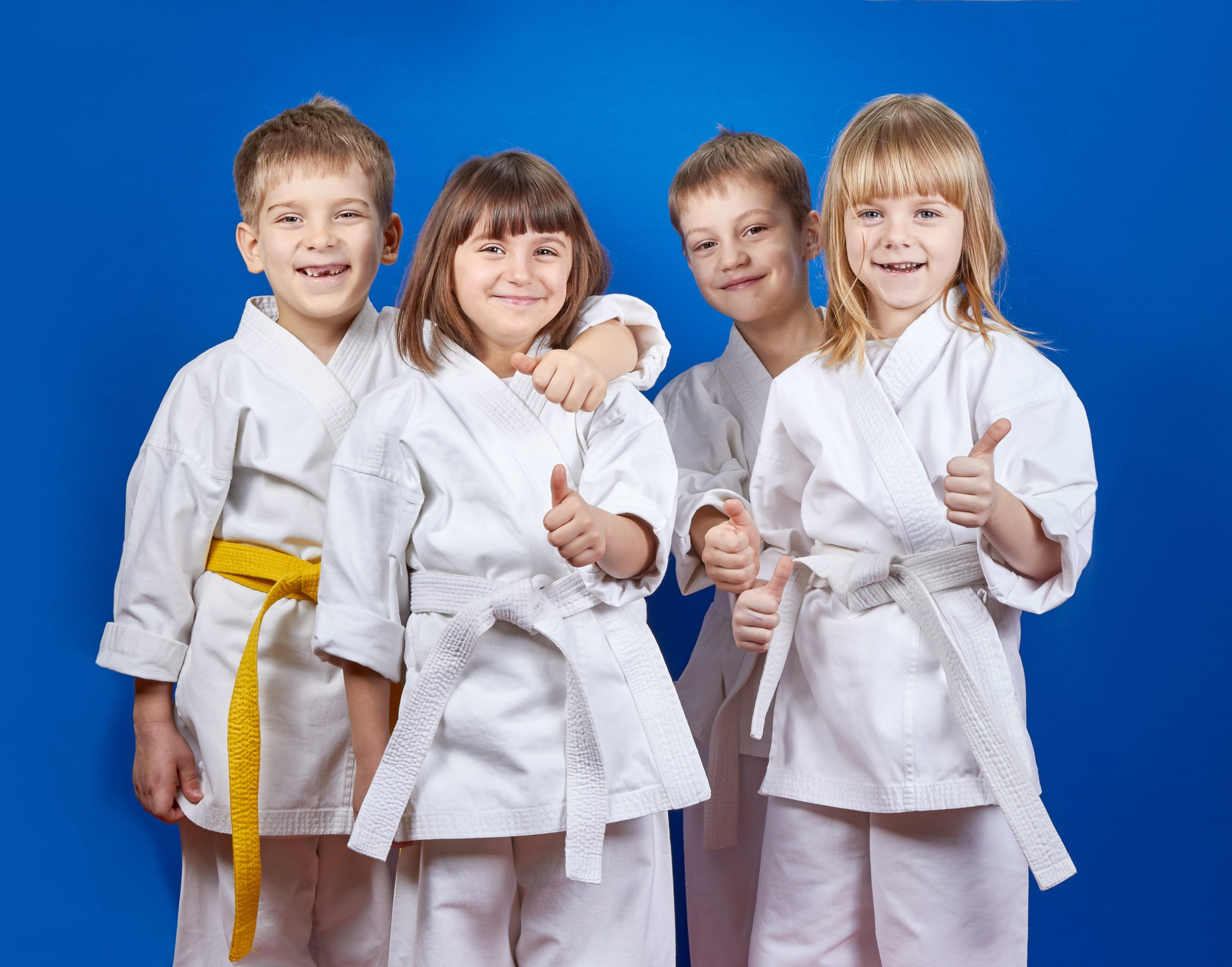 Four smiling boys and girls in karate outfits