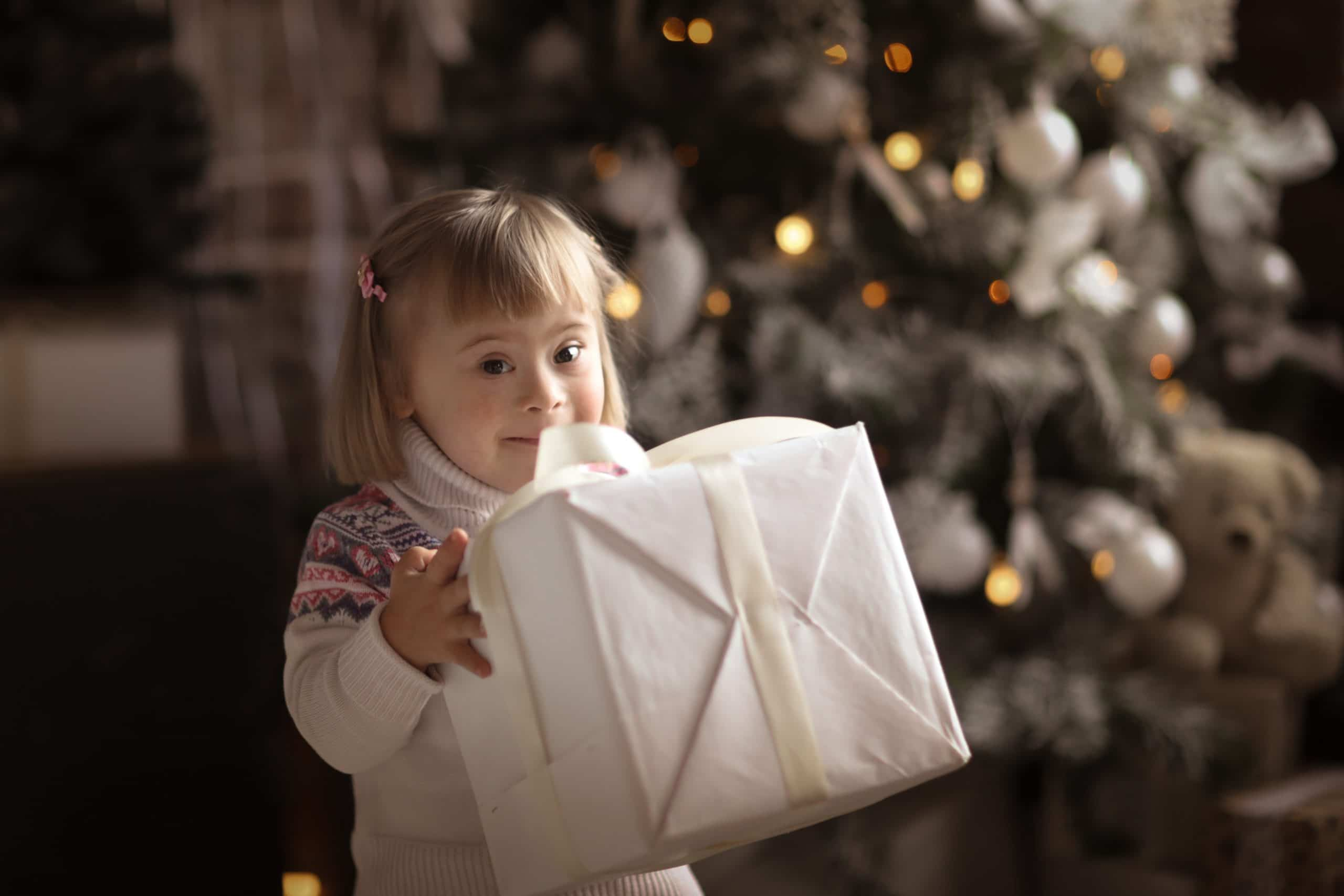 Young Girl with Christmas Present next to a Christmas Tree