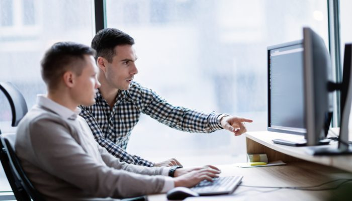 Two Men in Office Looking at a Computer