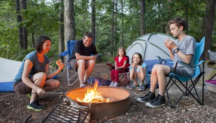 Family of five sitting around a campfire