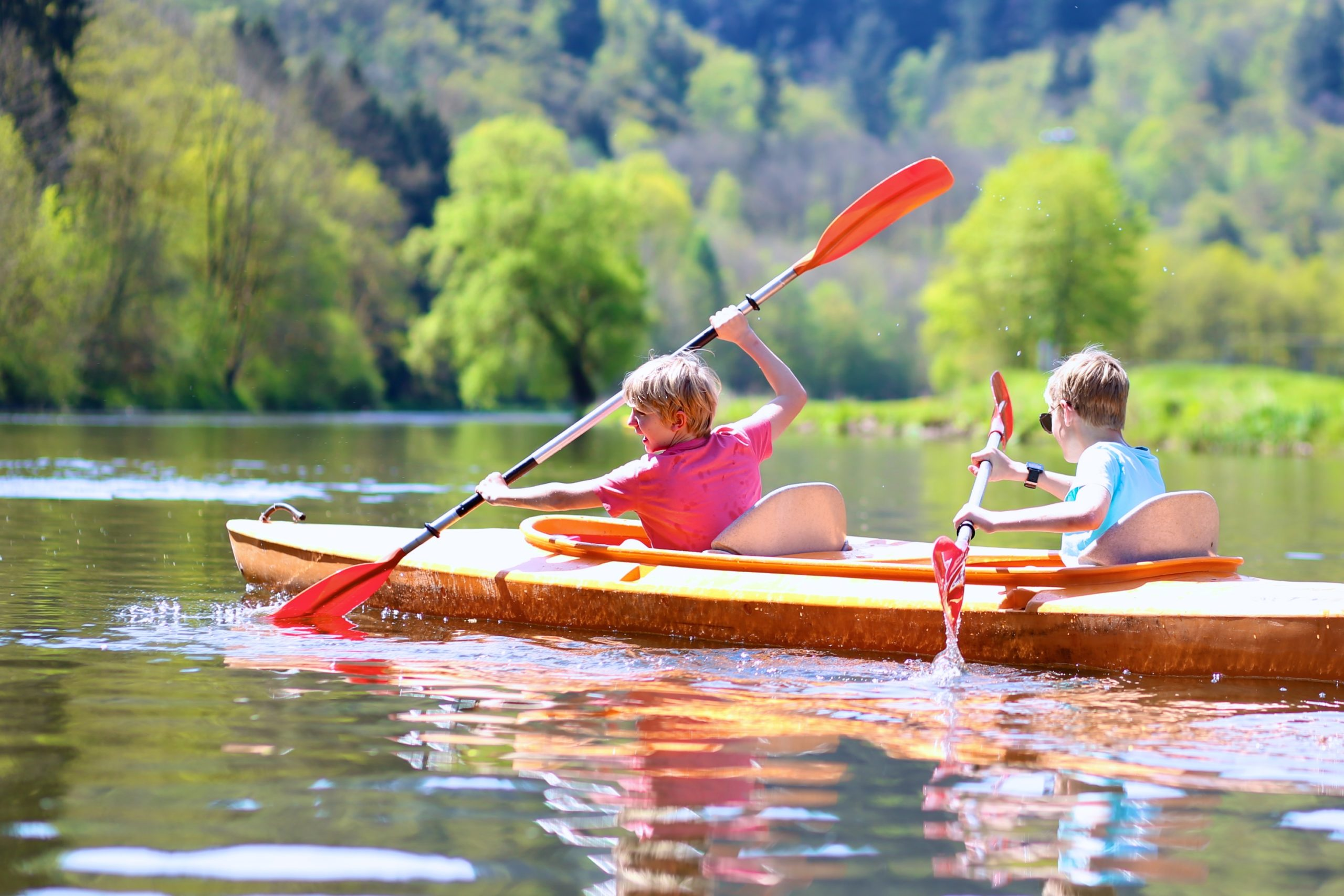 Two Boys Paddling in a Kayak on a Lake