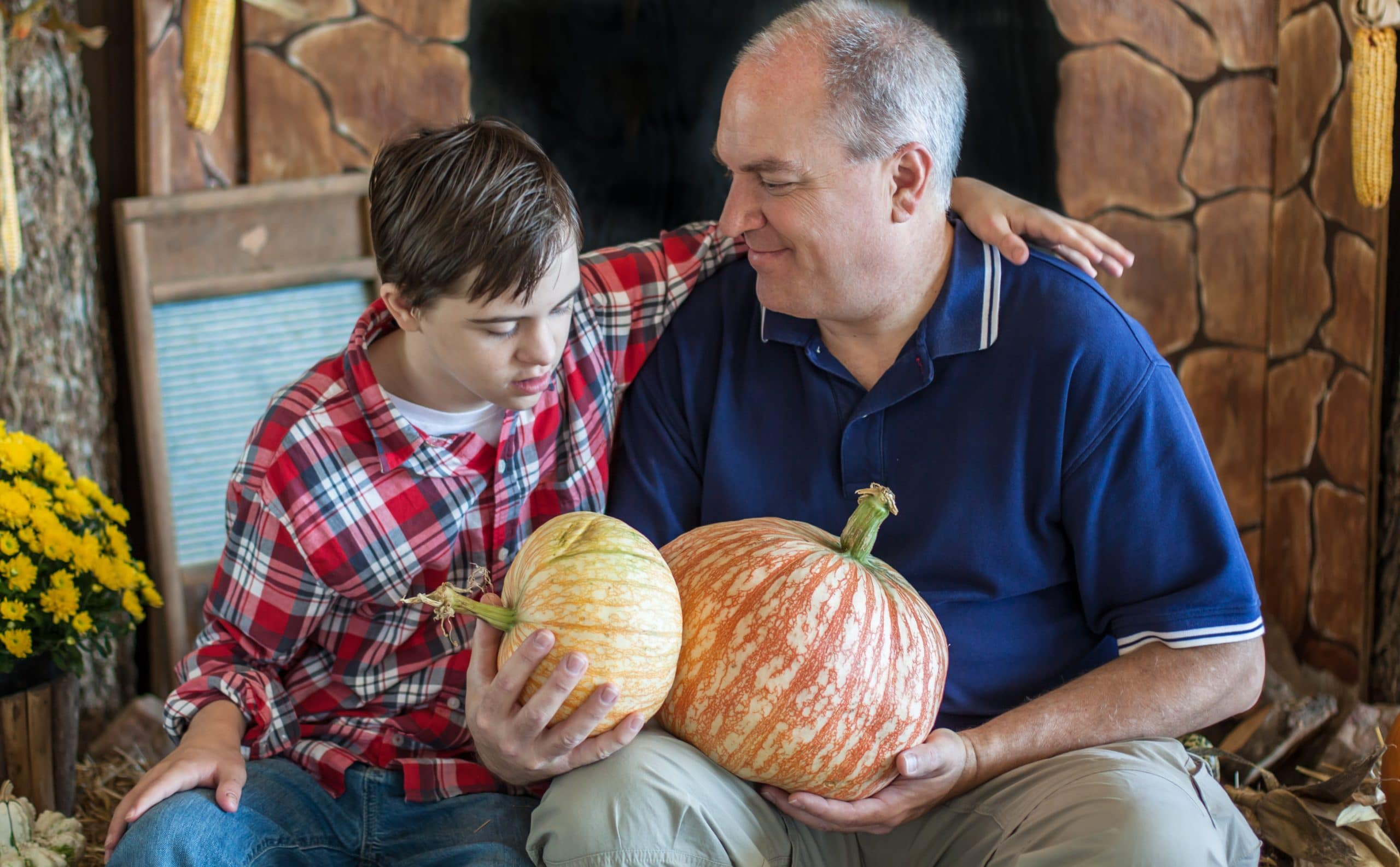 Boy with Autism Holding Pumpkins with his Grandfather