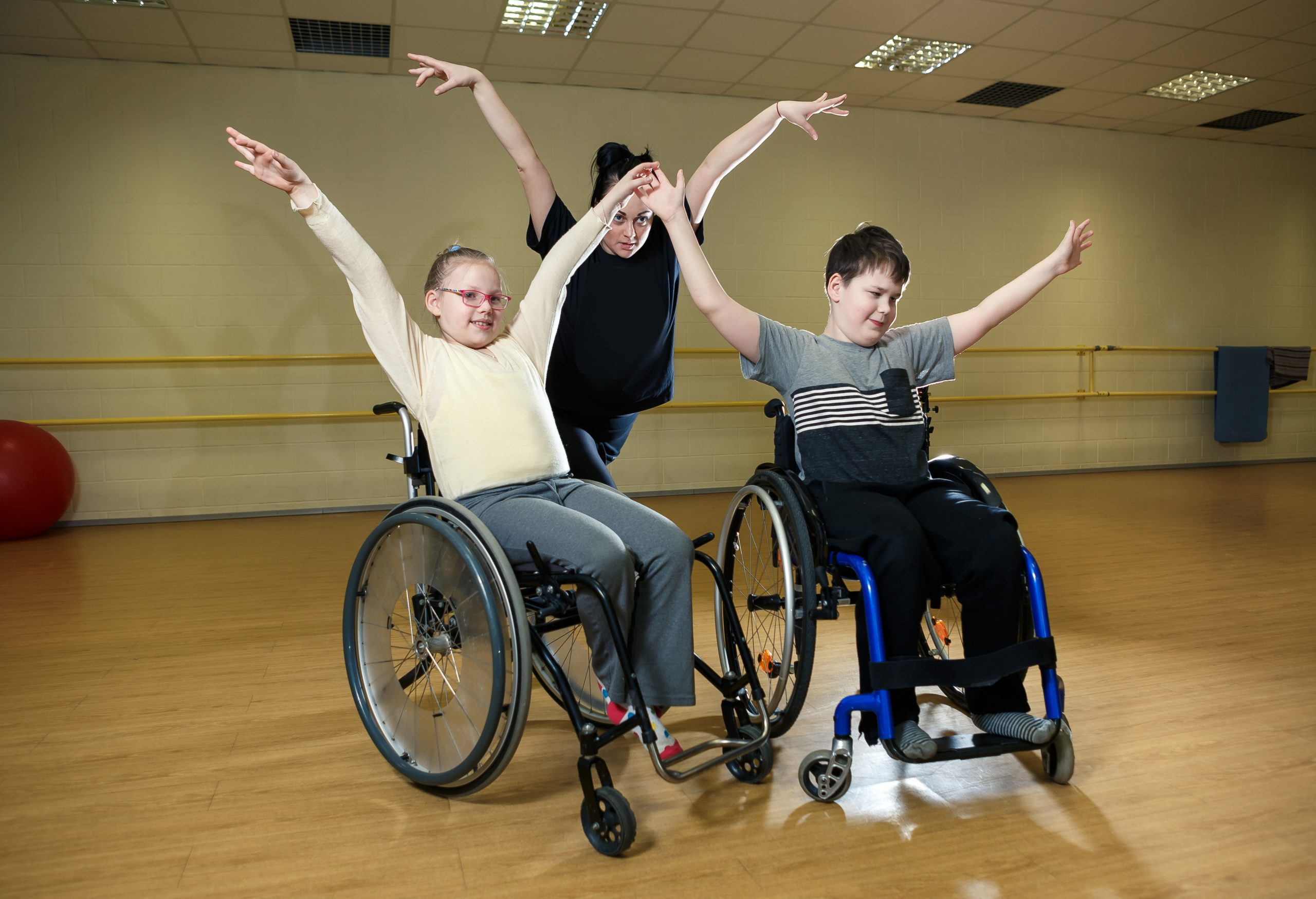 Two People in Wheelchairs Exercising in a Dance Studio